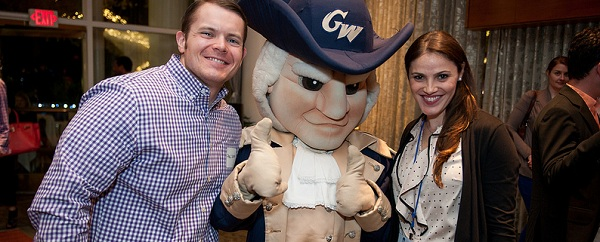 Alumni couple Paul Schuh and Alyscia Eisen pose with Big George during Alumni Weekend 2013. (Photo: Mike Kandel)