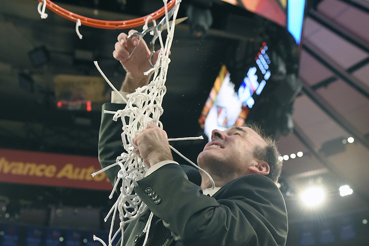 Coach Mike Lonergan cuts down the net following GW's win in the NIT Championship game (GW Athletics Communications)