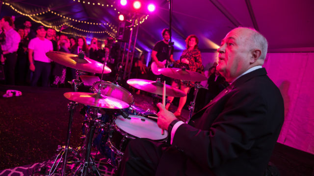 President Steven Knapp on the drums with White Ford Bronco at the Kickoff Party.